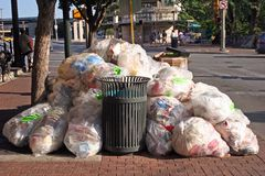Trash and garbage. Stacked outside on side walk near empty garbage can Stock Images