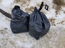Trash and garbage bags on snow royalty free stock images