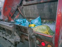 Trash or garbage day in the city. Close up of trash bags in garbage truck stock photography