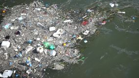 Trash and garbage floating on the surface of the water. Water pollution with dirt and plastic garbage floating on the surface of the sea stock footage