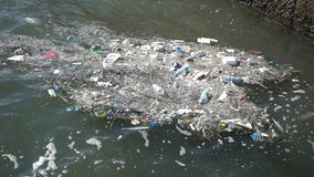 Trash and garbage floating on the surface of the water. Water pollution with dirt and plastic garbage floating on the surface of the sea stock video