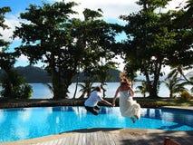Trash la sesión fotográfica de la boda del vestido que salta en una piscina Imagenes de archivo