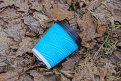Blue paper cup litter lies on dry brown leaves and grass royalty free stock image