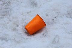 Orange plastic cup litter lying on white snow outside. Trash from one orange plastic cup lies on white snow outside stock image