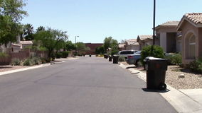 Trash pickup day. Trash cans ready for pickup line the street in a quiet neighborhood stock video