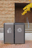 Trash and recycle bins. On public street outside brick building Stock Photo