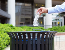 Trash recycling. Closeup portrait, hand throwing plastic empty water bottle in recycling bin, isolated building and trees background Royalty Free Stock Photography