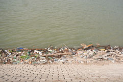 Trash at river bank Stock Images
