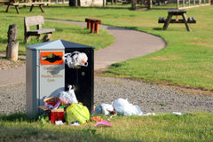 Trash or rubbish bin overflowing. Trash, garbage or litter bin in a park overflowing and litter all over the ground. Litter includes plastic bags Stock Image