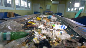 Trash, rubbish, litter on a working sorting conveyor belt in a recycling plant. stock footage