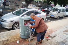 In the trash rummaging the old beggar Stock Images