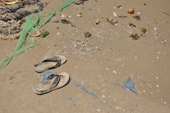 Trash on sand, and a pair of flip flops stock photos
