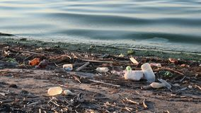 Trash on shore with dirty water. Large amount of trash on shore polluting our waters stock video footage