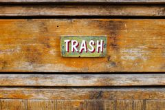 Trash sign on an old garbage receptacle. Hand-painted vintage trash sign on an old, weathered garbage receptacle stock photos