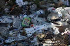 Trash site with a rusty wire fence. Trash site protected with a wire fence and a plastic green net stock photography