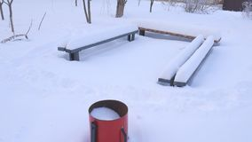 Trash with snow. Benches in the snow. Snowy winter. stock footage