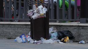 Trash spilling out of overfilled trash plastic bag on city street. Trash spilling out of overfilled trash plastic bag on city street stock video