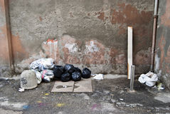 Trash in the street. Crowded trash on a wall in the street Stock Photography