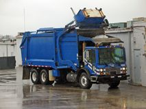 Trash Truck. Blue garbage truck collecting trash in the rain Stock Photo