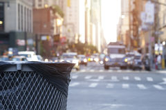 Trash waste bin on new york city street with people and cars wit. H traffic and copyspace for text and wording Royalty Free Stock Photo