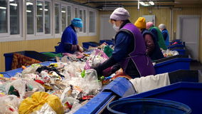 Trash workers sorting trash, garbage at a recycling plant conveyor. stock footage