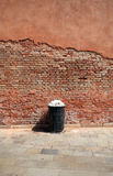 Trashcan filled against a red brick wal Royalty Free Stock Images