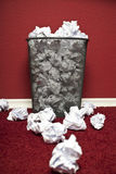 Trashcan filled with rumpled paper. Trashcan in front of red office wall filled with rumpled paper Stock Image
