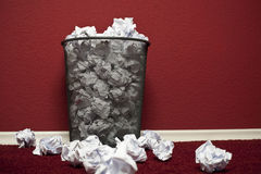 Trashcan filled with rumpled paper. Trashcan in front of red office wall filled with rumpled paper Royalty Free Stock Photography