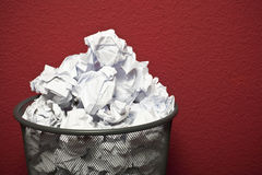 Trashcan filled with rumpled paper. Trashcan in front of red office wall filled with rumpled paper Stock Photo