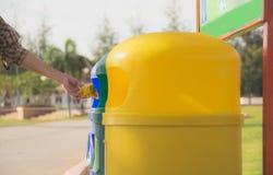 Trashcan plástico azul y amarillo en el parque en el verano Fotos de archivo