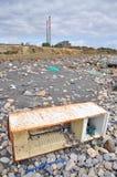 Trashed fridge on the seashore. Next to a factory Stock Photo