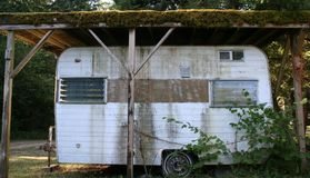 Trashy Trailer. Small and grungy looking trailer in a rural setting royalty free stock photo