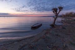 Trasimeno湖翁布里亚美丽的景色黄昏的,与在光秃的树、完全仍然水和a附近的一条小的小船 图库摄影