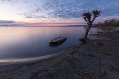 Trasimeno湖翁布里亚美丽的景色黄昏的,与在光秃的树、完全仍然水和a附近的一条小的小船 免版税库存照片