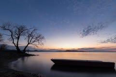 Trasimeno湖翁布里亚美丽的景色黄昏的,与在前景的一个小的小船剪影,完全仍然 库存照片