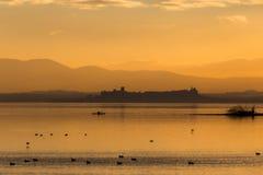 Trasimeno湖翁布里亚,日落的意大利美丽的景色,与橙色口气,在水的鸟,独木舟的一个人和 免版税库存图片