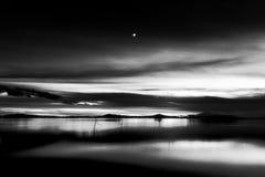 Trasimeno湖翁布里亚,黄昏的意大利美丽的景色,与黑白口气和月亮在天空 免版税库存照片