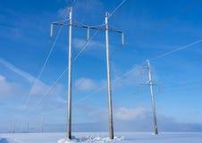 Trasmissione di energia elettrica nel campo contro il cielo blu fotografie stock libere da diritti