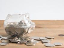 Trasparente veda attraverso il porcellino salvadanaio riempito di monete su fondo di legno immagini stock