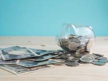 Trasparente veda attraverso il porcellino salvadanaio riempito di monete su fondo di legno Concetto di colore di investimento di  immagini stock libere da diritti