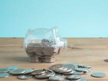Trasparente veda attraverso il porcellino salvadanaio riempito di monete su fondo di legno Concetto di colore di investimento di  immagini stock