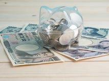 Trasparente veda attraverso il porcellino salvadanaio riempito di monete su fondo di legno Pila di cassaforte dei soldi fotografie stock