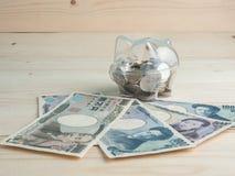 Trasparente veda attraverso il porcellino salvadanaio riempito di monete su legno immagini stock