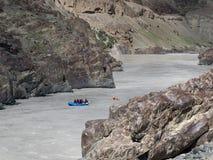 Trasportando su un fiume della montagna in una gola rocciosa stretta è navigato in barca blu con la gente e piccola barca rossa c Immagini Stock