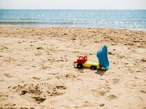 Trasporti il giocattolo su autocarro sulla spiaggia vuota sulla sabbia Immagine Stock