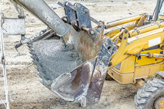 Trasporti il miscelatore su autocarro in corso di calcestruzzo di versamento nel mestolo del bulldozer Fotografie Stock