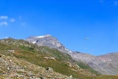 Trasporti il volo dell'elicottero con i rifornimenti ed il panorama della montagna con la capanna alpina, le alpi di Hohe Tauern, Fotografie Stock