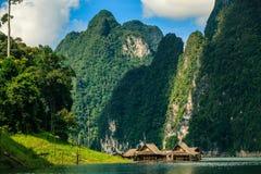 Trasporti la casa con una zattera sul fiume con la montagna su fondo Fotografie Stock
