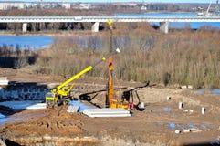 Trasporti la gru ed il piledriver su autocarro al cantiere durante gli impianti industriali - osservi il fron la cima Immagini Stock