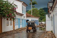 Trasporto che passa dalla pozza dell'acqua in vicolo del ciottolo, vecchie case in Paraty Fotografie Stock